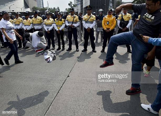 Demonstrators kick a donkey representing Mexican President Enrique Pena Nieto in front of a line of policemen during a teachers protest in Mexico...