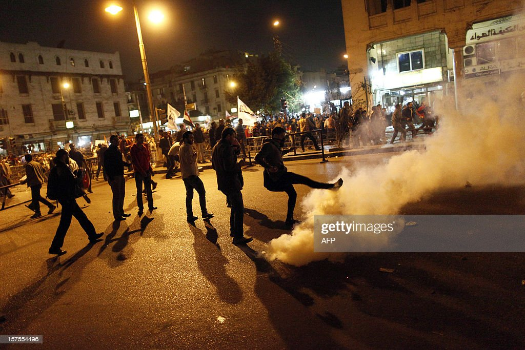 Demonstrators kick away a tear gas canister as they remove barrier from outside the Egyptian Presidential Palace's main gate during a demonstration on December 4, 2012 in Cairo. Tens of thousands of demonstrators encircled the presidential palace after riot police failed to keep them at bay with tear gas, in a growing crisis over President Mohamed Morsi's decree widening his powers.