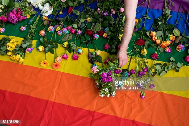 Demonstrators lay roses on a rainbow flag as they protest over an alleged crackdown on gay men in Chechnya outside the Russian Embassy in London on...