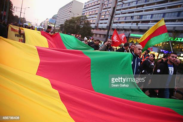 Demonstrators many of them members of Berlin's large Kurdish community march with a giant Kurdish flag to protest against the ongoing violence by...