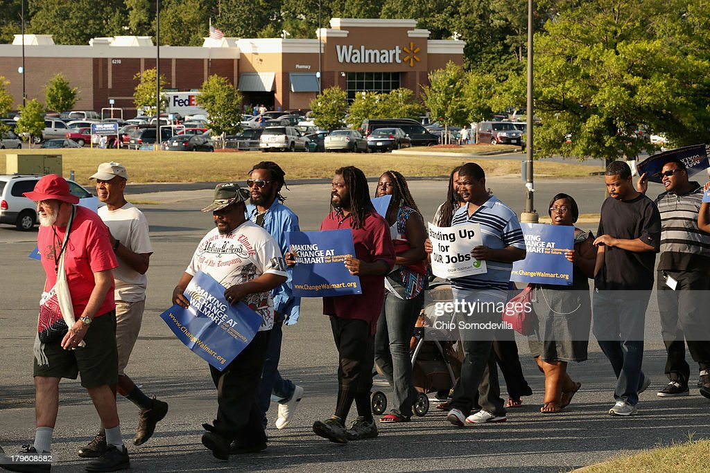 Demonstrators march and block traffic in a major intersection outside a Walmart store during rush hour September 5, 2013 in Hyattsville, Maryland. Six women were arrested during the demonstration where about 225 people gathered outside the Walmart store to protest the retail giant's labor practices. A showdown continues between Walmart and the neighboring District of Columbia, where Mayor Vincent Gray could sign a bill that would make large retailers to pay their employees a 50 percent premium over the city's minimum wage.