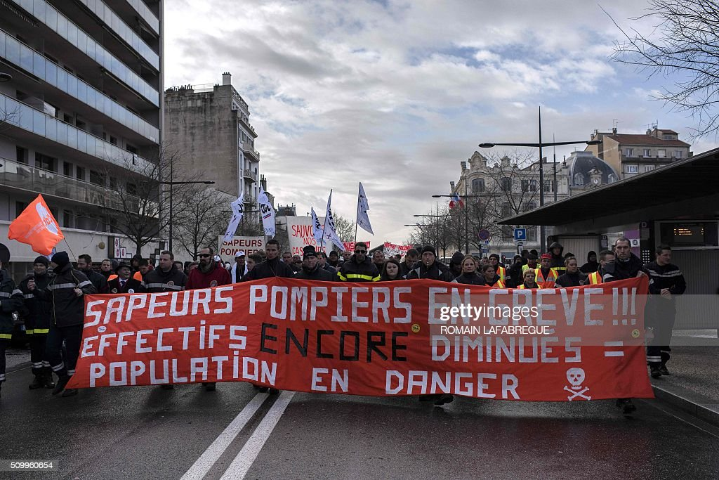 Demonstrators march behind a banner 'Firefighters on strike ! Decreased workforce = population on danger' during a demonstration to protest against the closure of 19 emergency services and fire centers, in Valence central eastern France, on February 13, 2016. / AFP / ROMAIN LAFABREGUE