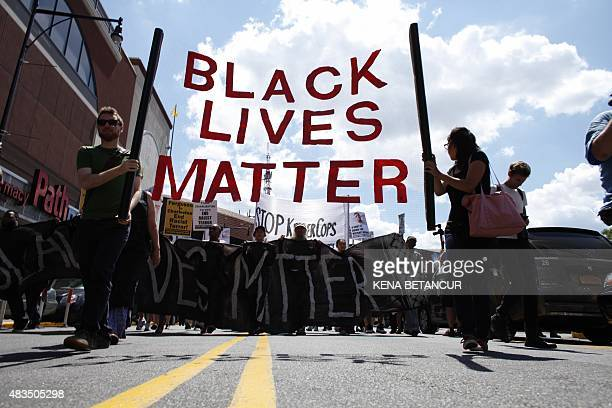 Demonstrators march during a Michael Brown memorial protest in Brooklyn New York on August 9 2015 Demonstrators showed support Sunday on the one year...