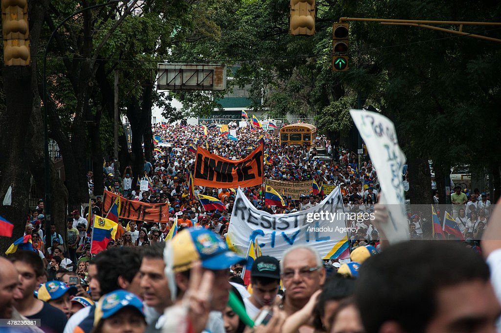 Demonstrators march during the anti-government protests in Caracas, Venezuela on March 12, 2014. Three people including a university student and a National Guard member, were shot death and several others injured on Wednesday during the anti-government protests in Venezuela.