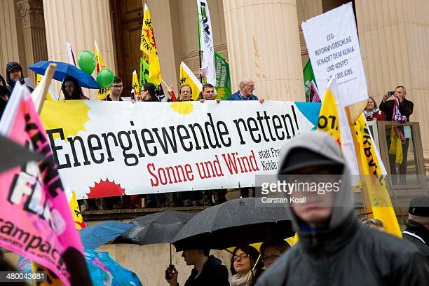 Demonstrators march holding a banner with the written slogan 'Energiewende retten Sonne und Wind' to demand a faster transition to renewable energy...