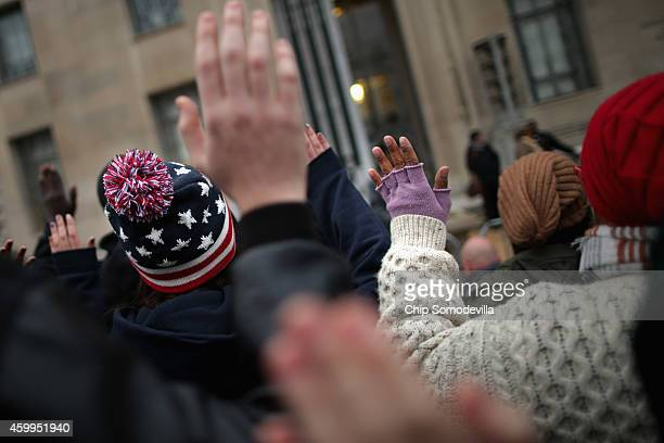 Demonstrators march in front of the Justice Department headquarters chanting 'Hands up Don't shoot' and 'I can't breath' in protest against recent...