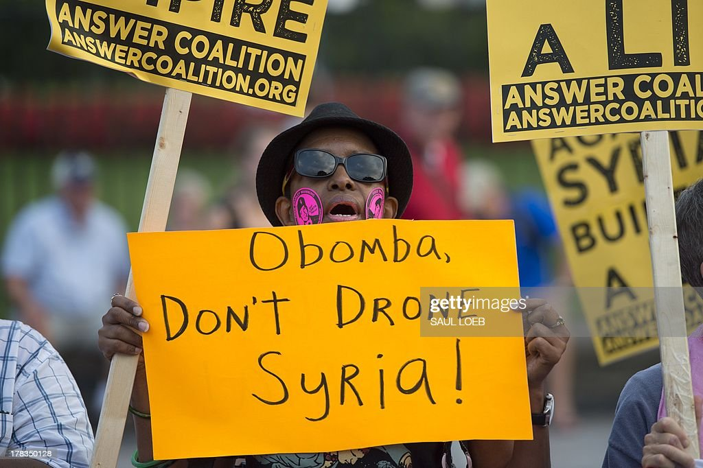 Demonstrators march in protest during a rally against a possible US and allies attack on Syria in response to possible use of chemical weapons by the Assad government, in Lafayette Park in front of the White House in Washington, DC on August 29, 2013. AFP PHOTO / Saul LOEB
