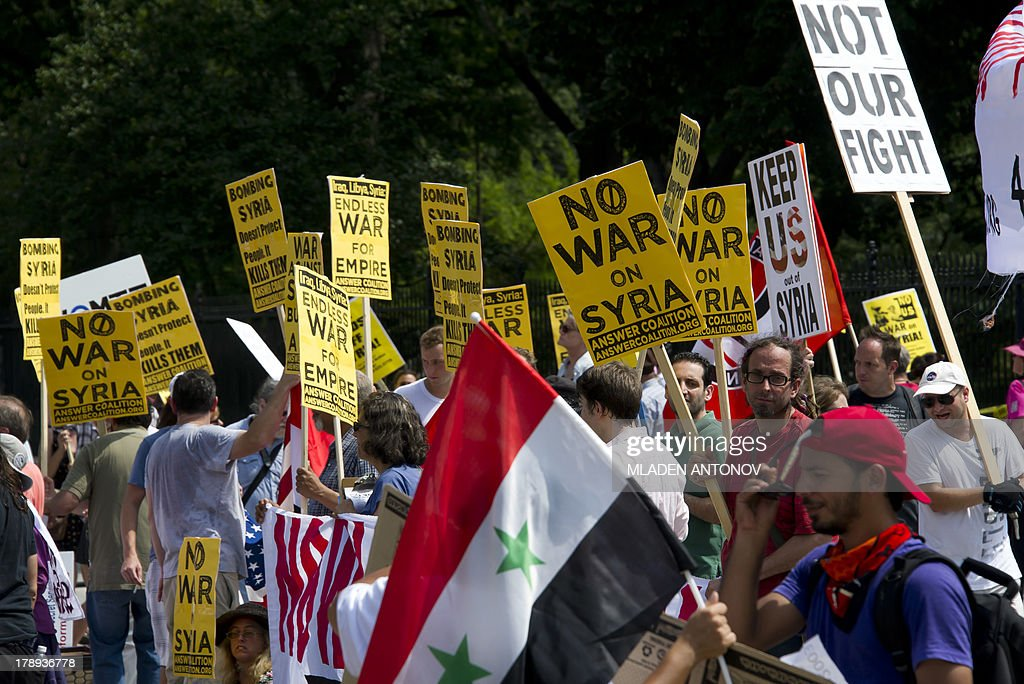 Demonstrators march in protest during a rally against a possible US attack on Syria in response to alleged use of chemical weapons by the Assad government, in Lafayette Park in front of the White House in Washington, DC on August 31, 2013. US President Barack Obama said Saturday he will ask the US Congress to authorize military action against Syria, lifting the threat of immediate strikes on President Bashar al-Assad's regime. Obama said he had decided he would go ahead and launch military action on Syria, but he believed it was important for American democracy to win the support of lawmakers. AFP PHOTO/MLADEN ANTONOV