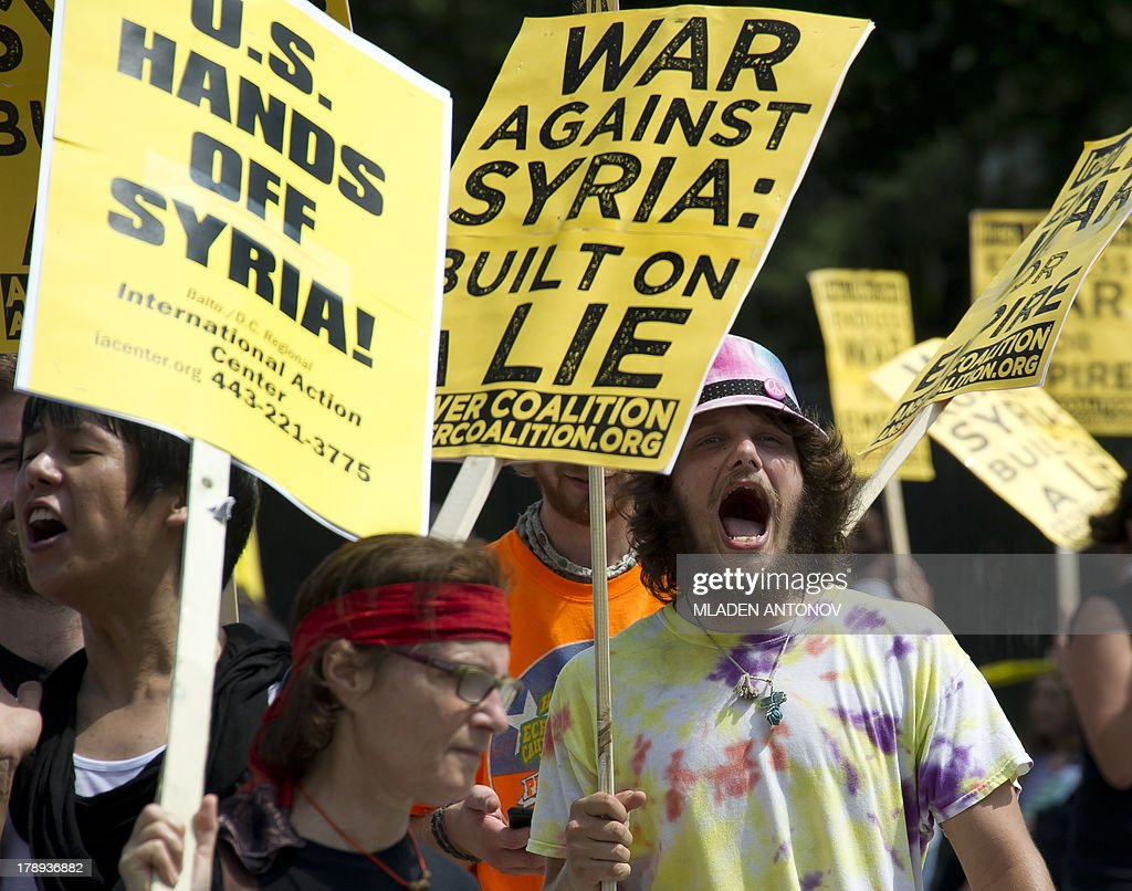 Demonstrators march in protest during a rally against a possible US attack on Syria in response to alleged use of chemical weapons by the Assad government, in Lafayette Park in front of the White House in Washington, DC on August 31, 2013. US President Barack Obama said Saturday he will ask the US Congress to authorize military action against Syria, lifting the threat of immediate strikes on President Bashar al-Assad's regime. Obama said he had decided he would go ahead and launch military action on Syria, but he believed it was important for American democracy to win the support of lawmakers.