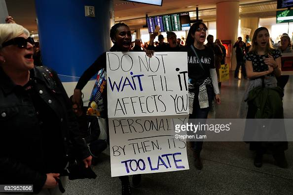 Demonstrators march into the international arrival area during a rally against muslim immigration ban at San Francisco International Airport on...