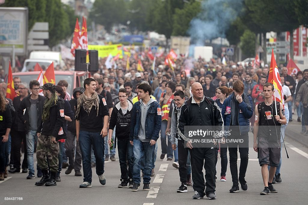 Demonstrators march on May 26, 2016 in Nantes, western France, during a protest against government planned labour law reforms. The French government's labour market proposals, which are designed to make it easier for companies to hire and fire, have sparked a series of nationwide protests and strikes over the past three months. Masked youths clashed with police and striking workers blockaded refineries and nuclear power stations on May 26 as an escalating wave of industrial action against labour reforms rocked France. / AFP / JEAN