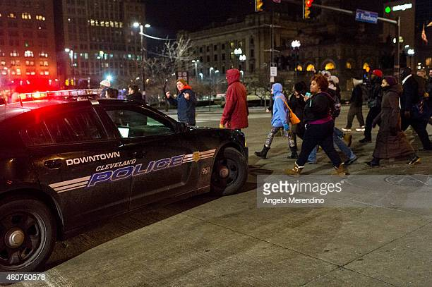 Demonstrators march past a police cruiser on S Roadway outside of Public Square December 21 in Cleveland Ohio Protestors gathered for the second...