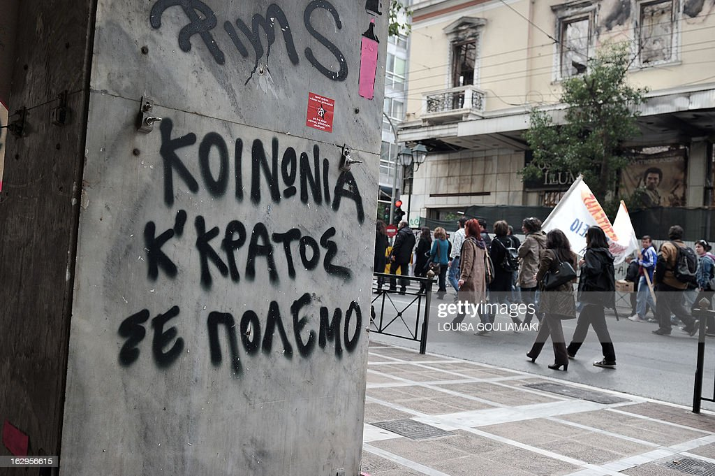 Demonstrators march past graffiti on a shut down hotel reading 'society and state in war' during a protest of Greek teachers and students in Athens on March 2, 2013 against cutbacks in the public education system due to the government's austerity measures. Demonstrators protested the lack of heat and food in many schools and the overall downgrade of public education.
