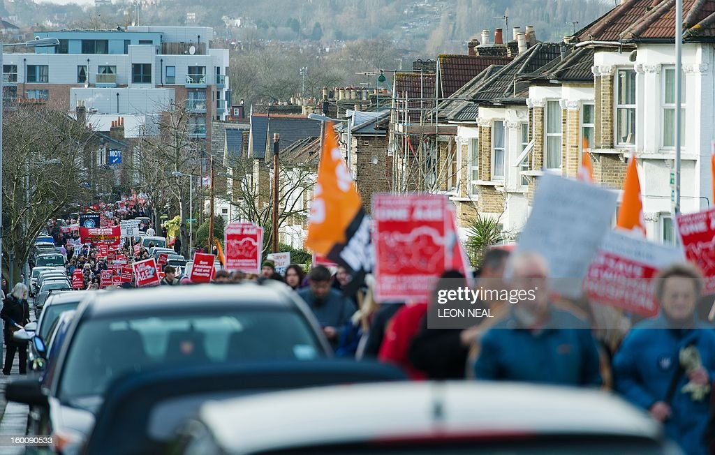 Demonstrators march past in South-East London on January 26, 2013 to protest against the proposed closure of the Accident and Emergency (A&E) and maternity units at Lewisham hospital. A Government-appointed administrator has recommended that the units be shut down to help tackle the financial crisis at the nearby South London Healthcare NHS Trust. Those protesting argue that leaving a single A&E unit for up to 750,000 people is 'ludicrous and highly dangerous'. AFP PHOTO/Leon Neal