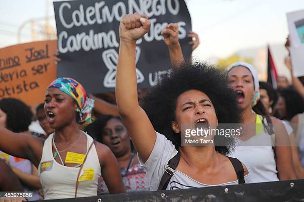 Demonstrators march through the Manguinhos favela to protest against police killings of blacks on August 22 2014 in Rio de Janeiro Brazil Every year...