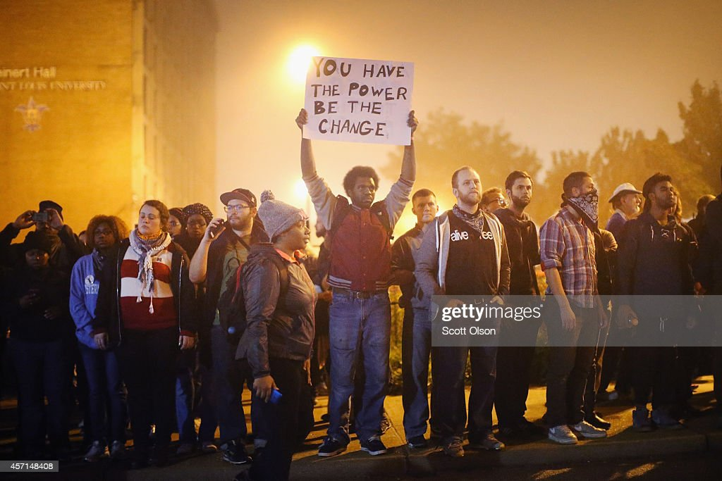 Demonstrators march through the street on October 13 2014 in St Louis Missouri The St Louis area has been struggling to heal since riots erupted...
