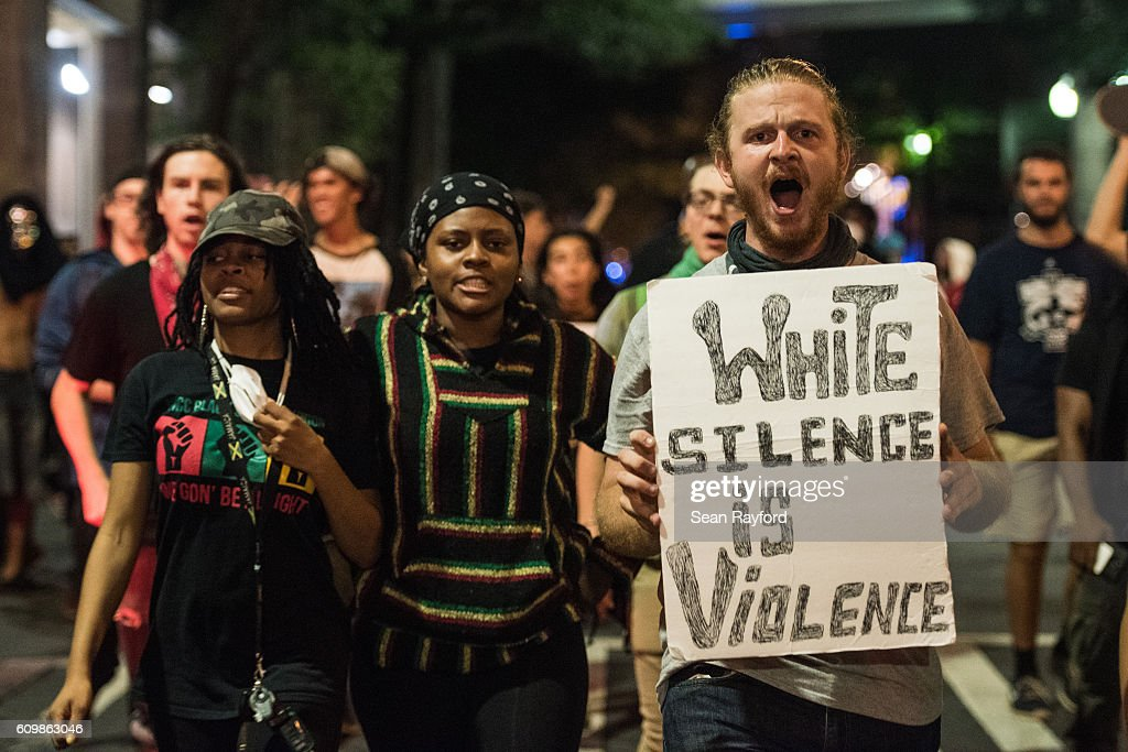 Demonstrators march together in protest on September 22, 2016 in Charlotte, NC. Protests began on Tuesday night following the fatal shooting of 43-year-old Keith Lamont Scott at an apartment complex near UNC Charlotte. A state of emergency was declared overnight in Charlotte and a midnight curfew was imposed by mayor Jennifer Roberts, to be lifted at 6 a.m.