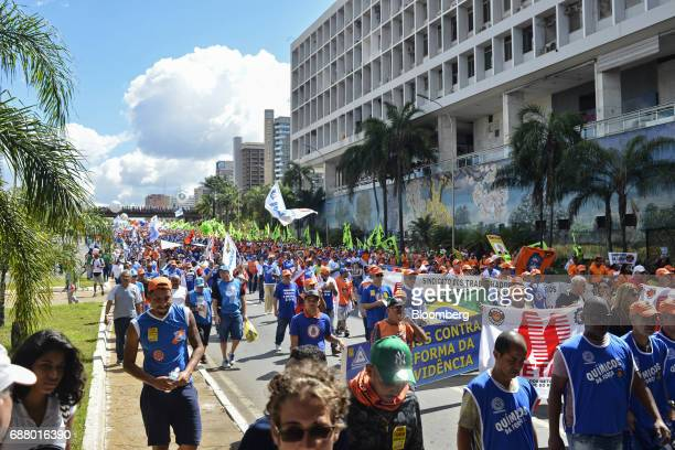 Demonstrators march while holding banners and flags during protests outside of the National Congress demanding the resignation of Brazilian President...