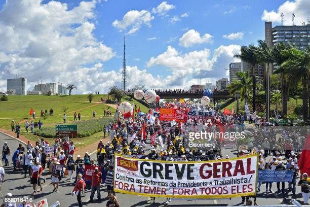 Demonstrators march while holding banners during protests outside of the National Congress demanding the resignation of Brazilian President Michel...