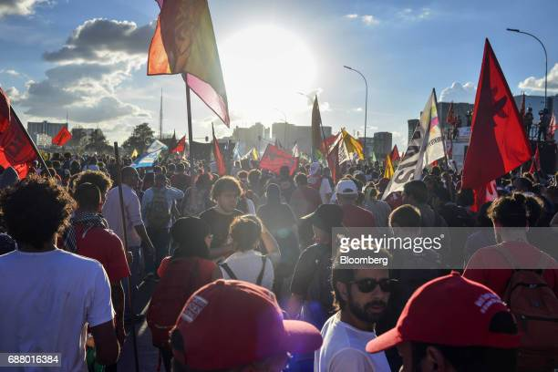 Demonstrators march while holding flags during protests outside of the National Congress demanding the resignation of Brazilian President Michel...