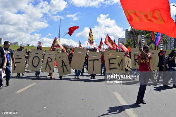 Demonstrators march while holding placards and flags during protests outside of the National Congress demanding the resignation of Brazilian...