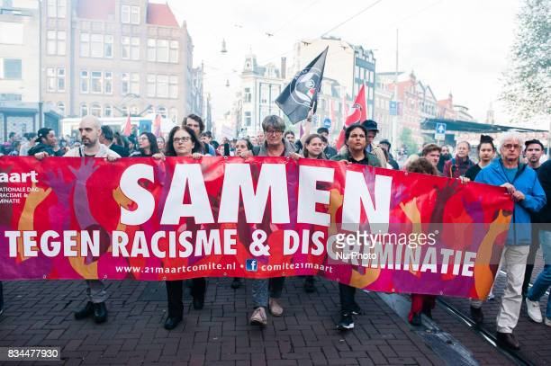 Demonstrators march with a banner during a protest called by the Dutch Antifascist Action AFA against the violence that took place at the August 12th...