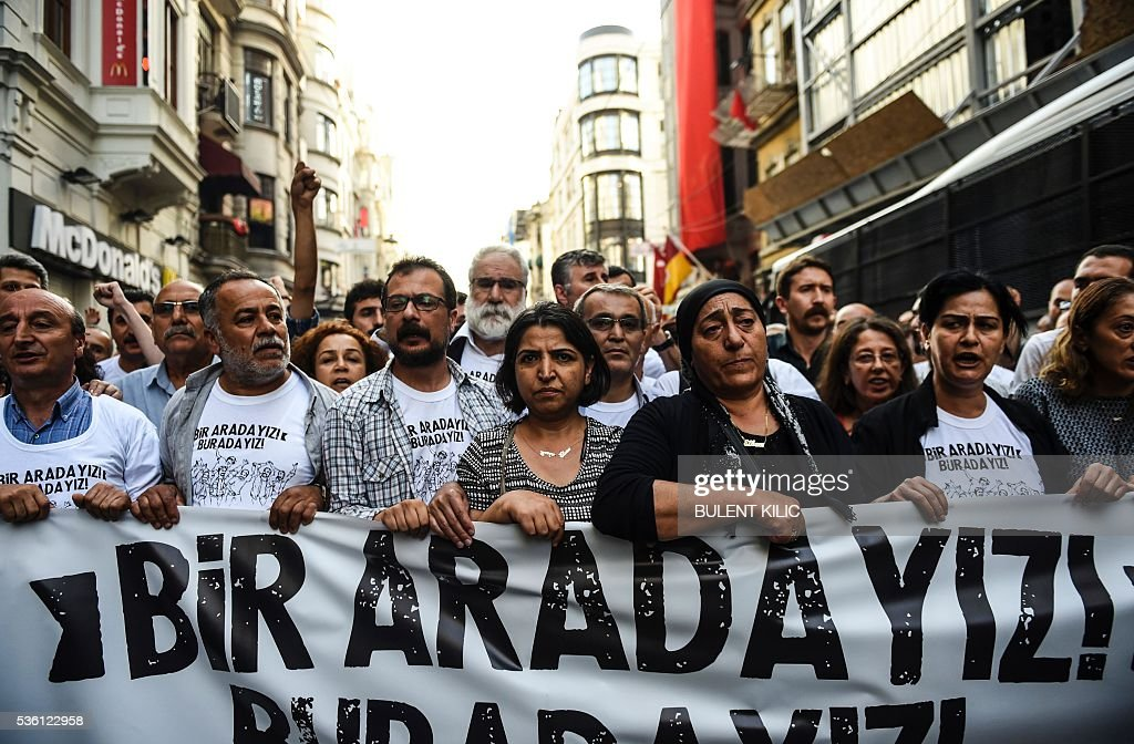 Demonstrators march with banners on May 31, 2016 in Istanbul, on the third anniversary of the start of the Gezi Park protests. The Gezi Park protests which began in May 2013, were sparked by the heavy-handed eviction of demonstrators staging a sit-in protest against the redevelopment of the area and grew into often violent clashes with police as people demonstrated against much broader issues concerning perceived infringements of civil rights. / AFP / BULENT