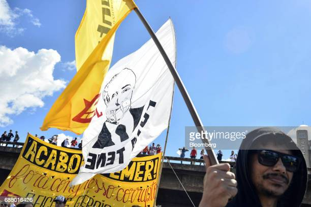 A demonstrators marches while holding a flag during protests outside of the National Congress demanding the resignation of Brazilian President Michel...