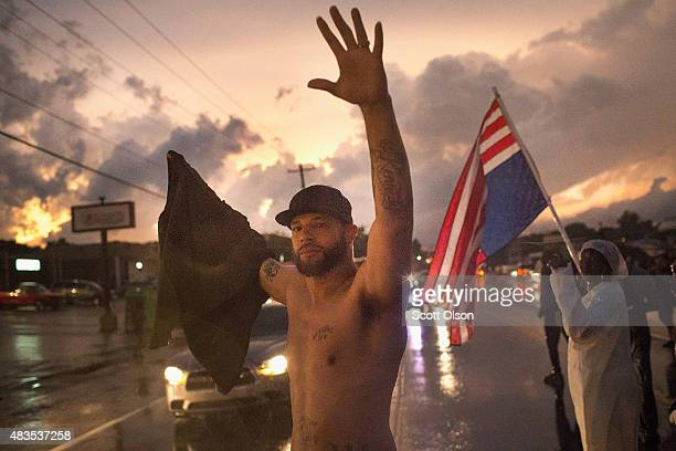 Demonstrators marking the oneyear anniversary of the shooting of Michael Brown march along West Florrisant Street in a driving rain on August 9 2015...