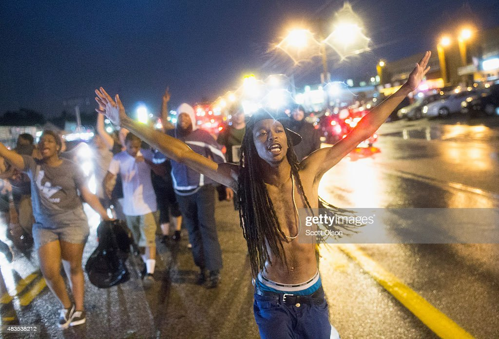 Demonstrators, marking the one-year anniversary of the shooting of Michael Brown, march along West Florrisant Street on August 9, 2015 in Ferguson, Missouri. There are reports that two people were shot when gun fire broke out during protests later in the evening. Brown was shot and killed by a Ferguson police officer on August 9, 2014. His death sparked months of sometimes violent protests in Ferguson and drew nationwide focus on police treatment of black suspects.