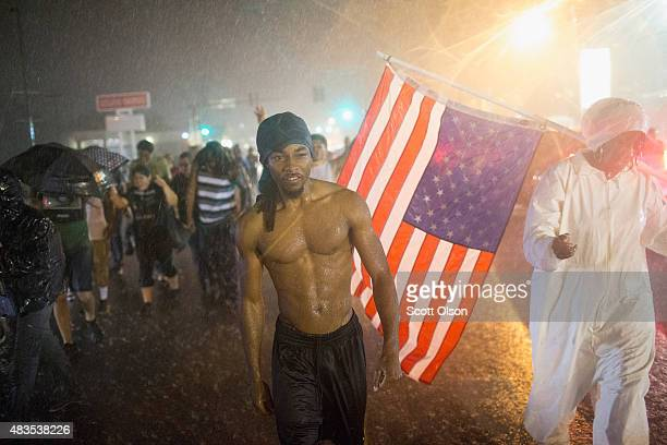 Demonstrators marking the oneyear anniversary of the shooting of Michael Brown march along West Florrisant Street in the driving rain on August 9...