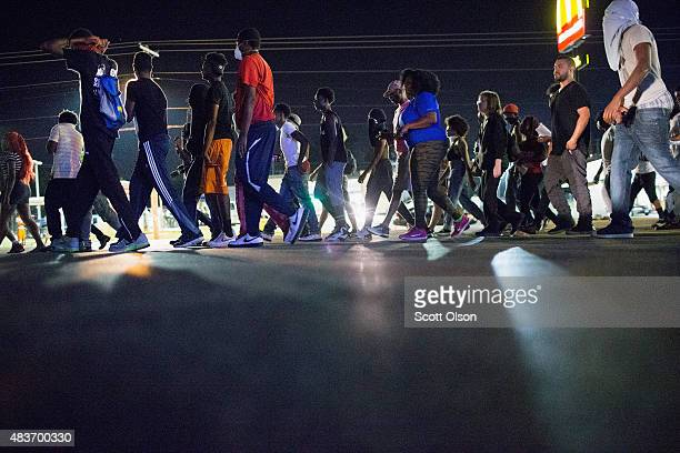 Demonstrators marking the oneyear anniversary of the shooting of Michael Brown confront police during a protest along West Florrisant Street on...