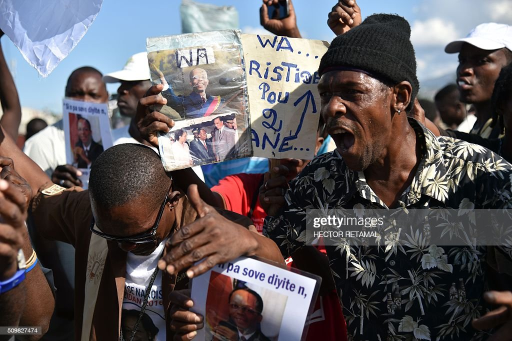 Demonstrators of opposition political parties manifest in front of the Haitian Parliament, during a march in Port-au-Prince, on February 12, 2016, to ask for Jocelerme Privert, current president of the senate to take the provisional presidency of Haiti for a period of two years. Election for a provisonal president will be held on Saturday 13th by the National Assembly and installation is scheduled on Sunday 14th. / AFP / HECTOR RETAMAL