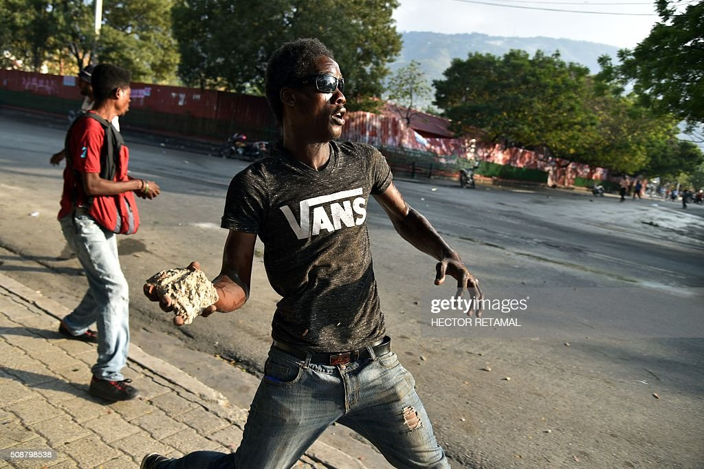 Demonstrators of opposition political parties throw stones at police during a protest against Haitian President Michel Martelly, in Port-au-Prince, on February 6, 2016. Haitian politicians inked a last-minute agreement to install a transitional government, just hours before President Michel Martelly was scheduled to step down with no replacement in line. / AFP / HECTOR RETAMAL