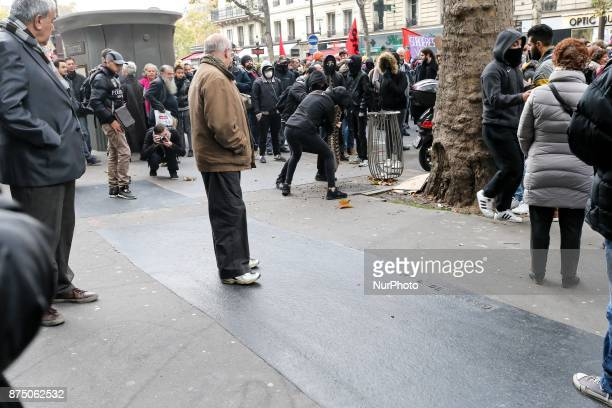 Demonstrators of ultraleft get a grate off the pavement during a demonstration as part of a nationwide protest day against the government's economic...