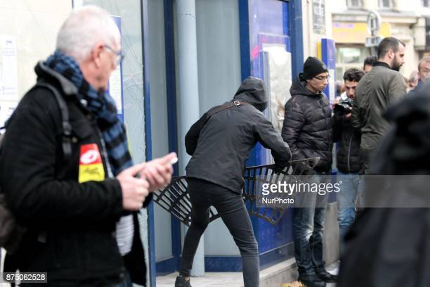 Demonstrators of ultraleft get throw a grate against the windows of a bank during a demonstration as part of a nationwide protest day against the...