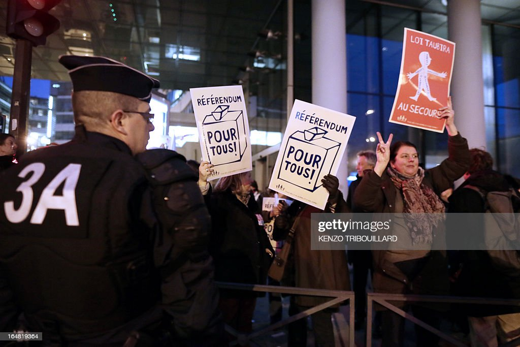 Demonstrators opposed to same-sex marriage hold placards reading 'Referenda for all' during a protest on March 28, 2013 outside the headquarters of France Television group in Paris, while the French president is interviewed during the broadcast news on the TV channel France 2.
