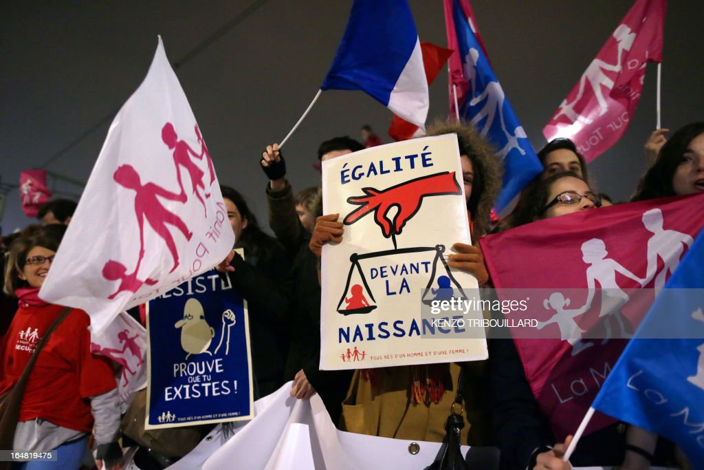 Demonstrators opposed to same-sex marriage wave flags and hold placards during a protest on March 28, 2013 outside the headquarters of France Television group in Paris, while the French president is interviewed during the broadcast news on the TV channel France 2. AFP PHOTO / KENZO TRIBOUILLARD