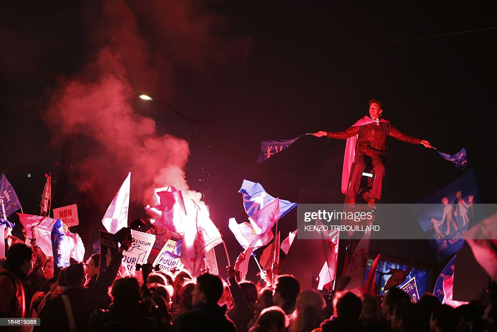 Demonstrators opposed to same-sex marriage wave flags and use flares during a protest on March 28, 2013 outside the headquarters of France Television group in Paris, while the French president is interviewed during the broadcast news on the TV channel France 2.