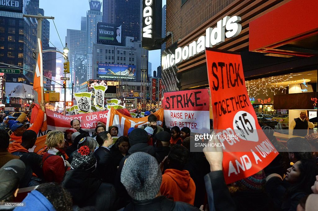 Demonstrators outside a McDonald's restaurant near New York's Times Square as part of a nationwide protest of fast food workers December 5, 2013. Fast-food workers say they will sponsor one-day strikes in 100 cities on Thursday and protest activities in 100 additional cities to demand McDonalds, Burger King, Taco Bell, Wendy's and other fast-food restaraunts to pay a $15-an-hour wage. AFP PHOTO/Stan HONDA