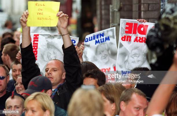 Demonstrators outside the Prince's Foundation building in Shoreditch London wave banners as the Prince of Wales accompanied by his partner Camilla...