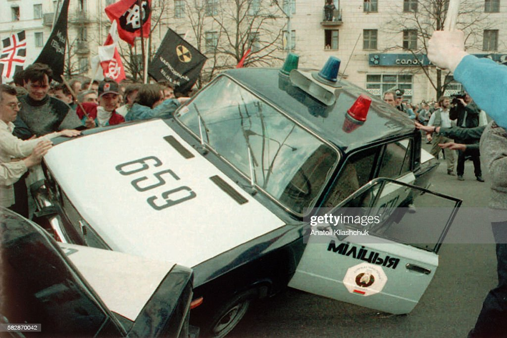 Demonstrators overturn a police car as a nonviolent demonstration degrades following police force against the participants of the peaceful...