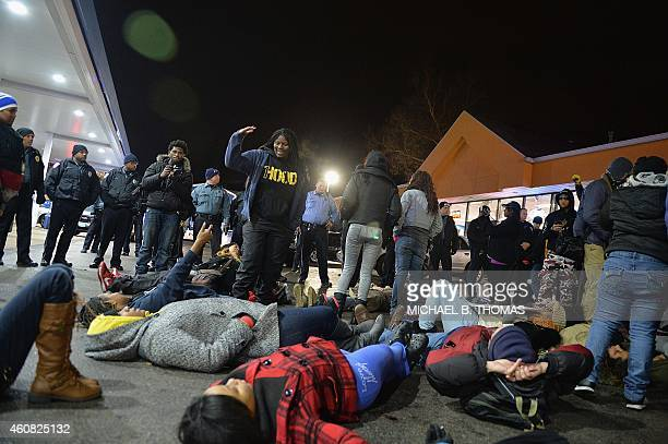 Demonstrators participate in a diein protest outside the Mobil OnTheRun gas and convenience store in Berkeley Missouri on December 24 2014 In the...
