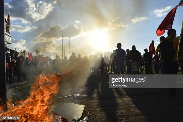 Demonstrators pass a fire while marching towards the National Congress during protests demanding the resignation of President Michel Temer in...