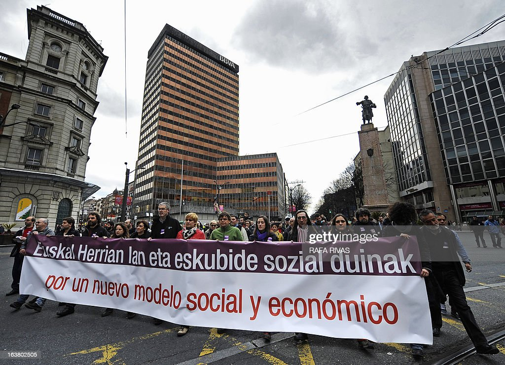 Demonstrators pass Spanish bank BBVA headquarters as they protest against government's austerity measures during a demonstration called by several Basque unions and social collectives in the Northern Spanish Basque city of Bilbao on March 16, 2013. The banner reads in Basque and Spanish 'Decent jobs and social rights in the Basque Country. In favour of a new social and economic model'.