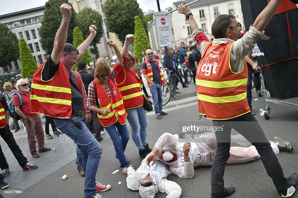 Demonstrators perform a fight between CGT trade union and France's employer federation Medef during a protest against controversial labour reforms, on June 28, 2016 in Nantes, western France. People took to the streets in France on June 28 in the latest protest march in a marathon campaign against the French Socialist government's job market reforms. Last month the government used a constitutional manoeuvre to push the bill through the lower house without a vote in the face of opposition from Socialist backbenchers. / AFP / LOIC