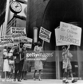 Demonstrators picket in front of a school board office protesting segregation of students