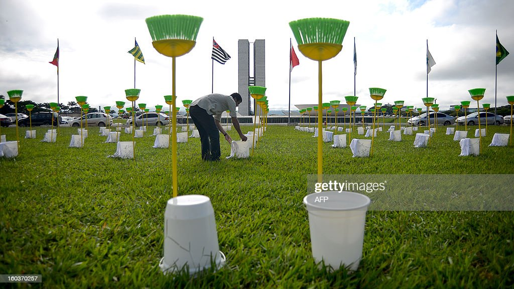 Demonstrators place 81 cleaning kits consisting each in a broom, a bucket and a duster in front of the Brazilian National Congress, in Brasilia, on January 30, 2013. The demonstration is organized by Rio de Janeiro's 'River of Peace' movement and the 81 cleaning kits --the number of senators of in the national congress-- symbolizes the need for 'cleaning' the senate of corruption. This week the presidential election will be held in the federal senate and the favorite candidate, senator Renan Calheiros, has been the target of many accusations of corruption. AFP PHOTO/PEDRO LADEIRA
