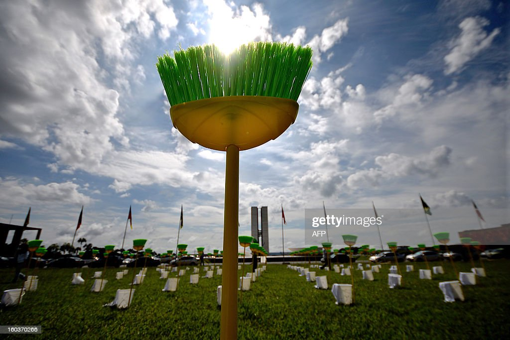 Demonstrators place 81 cleaning kits consisting each in a broom, a bucket and a duster in front of the Brazilian National Congress, in Brasilia, on January 30, 2013. The demonstration is organized by Rio de Janeiro's 'River of Peace' movement and the 81 cleaning kits --the number of senators of in the national congress-- symbolizes the need for 'cleaning' the senate of corruption. This week the presidential election will be held in the federal senate and the favorite candidate, senator Renan Calheiros, has been the target of many accusations of corruption.
