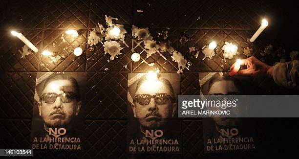 Demonstrators place candles on the sidewalk beside posters with the portrait of late Chilean dictator general Augusto Pinochet with the inscription...